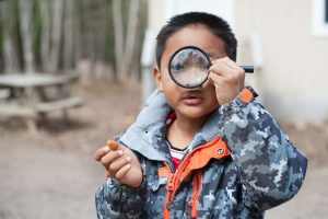 Kid looking through magnifier