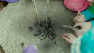 Kids playing with sticks and rocks