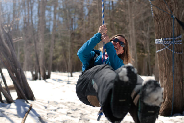Woman swinging on a rope swing outdoors in the winter