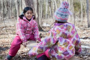 Two children sit on a seesaw in the forest