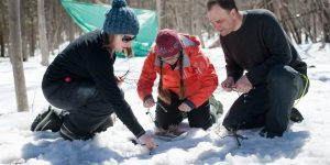 Three people holding twigs starting small fire in the snow