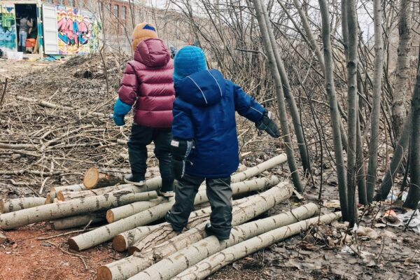 Two children walk over a pile of logs in the forest