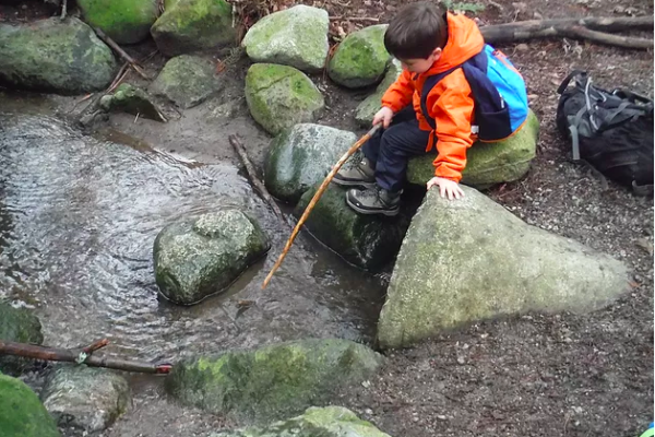 A child sits on top of a rock and explores a puddle with a long stick
