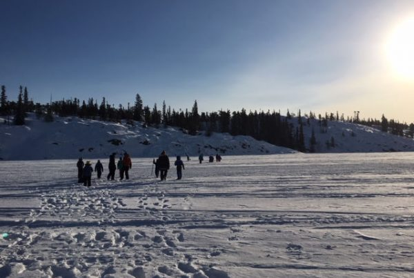 A group of people walking in a snowy field