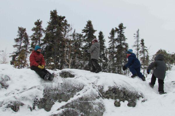 Three children climb a rocky hill covered in snow