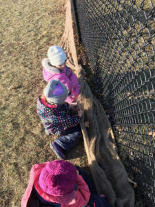 children sitting by a chain link fence