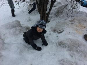 boy crawling on icy hill