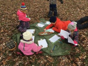 Kids drawing on clipboards on a tarp