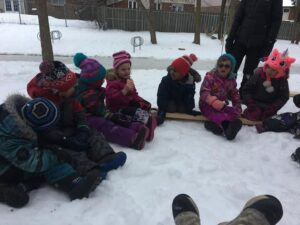 Kids sitting on planks of wood in the snow