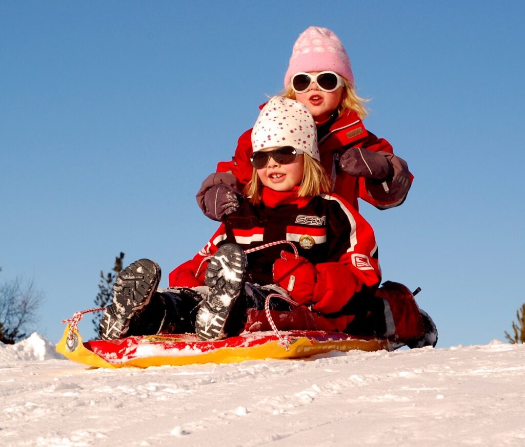 Two kids on a sled on top of a snowy hill
